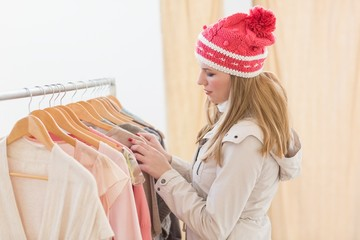 Pretty blonde looking at clothes on rail