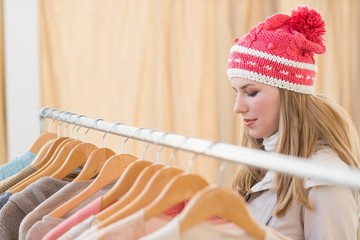 Close up of a pretty blonde looking at clothes on rail