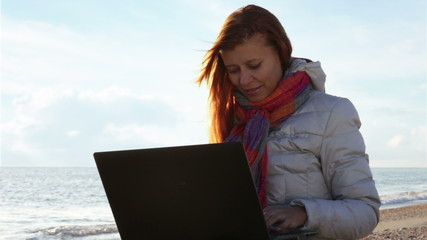 woman working on laptop at sea