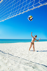 Kid play volleyball on sea beach
