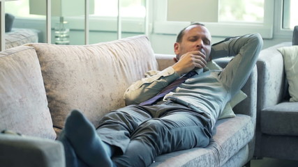 Attractive businessman yawning and sleeping on sofa at home
