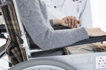Male doctor to encourage a wheelchair patient