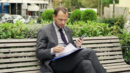Unhappy businessman comparing data on smartphone and documents s