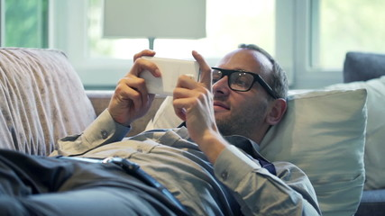 Young businessman playing game on smartphone and lying on sofa a