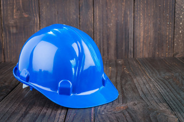Construction hard hat on wooden background