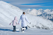 Mother and daughter walking in the mountains of the vast snow