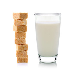 glass of milk and cubes of cane sugar isolated on white backgrou