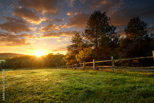 Leinwanddruck Bild Picturesque landscape, fenced ranch at sunrise