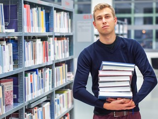 Student in library holding books