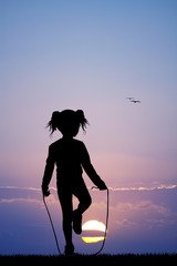 little girl juming with rope at sunset