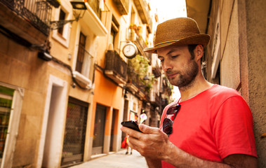 Tourist man looking at mobile phone - summer holiday