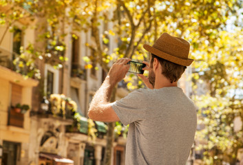Tourist man takes photo on mobile phone - summer holiday