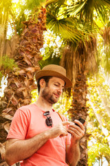 Tourist man looking at mobile phone - summer exotic holiday
