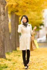 秋の歩道を歩く女性