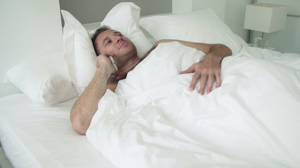 Young man talking on cellphone lying in bed at home