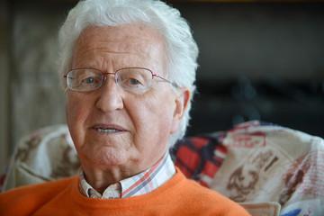Ritratto di anziano in casa seduto in poltrona