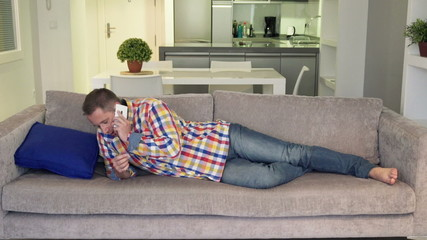 Man talking on cellphone and taking nap on sofa at home
