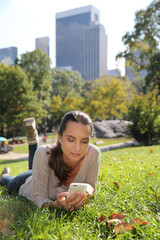 Young woman in Central Park using smartphone