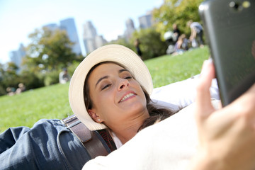 Woman relaxing on Central Park, using smartphone