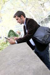 Businessman using digital tablet in city park