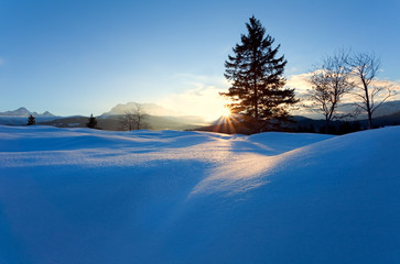 sunset over snow hills in Alps