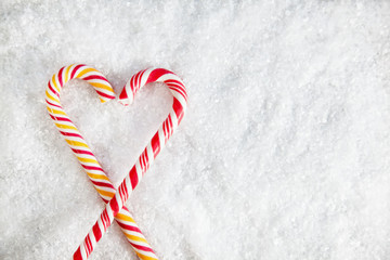 Two Candy Canes On Snowy Background