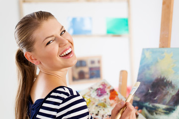 Smiling artist woman painting on canvas with acrylic colors
