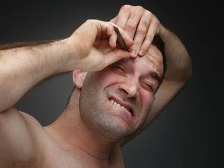 Young men pluck his eyebrows.