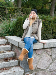Junge Frau mit Kaffeebecher im Park