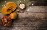 Rustic style pumpkins with seeds on green napkin and wood