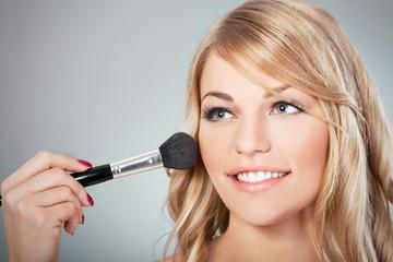 Beautiful blond fashion model applying blusher on cheeks