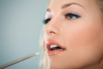 Beautiful woman applying make up on her lips