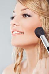 Beautician applying blusher on a cheek of beautiful model