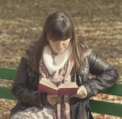 Beautiful woman sitting on a park bench and reading a book