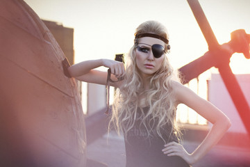 Fashion woman with long blond hair, make up and eye-patch