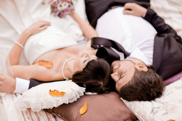 Bride and groom are in the maple leaves on pillow