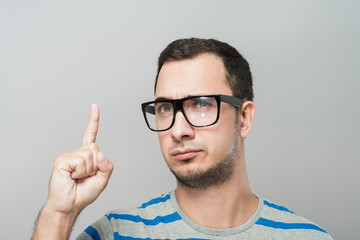Closeup portrait of young business man pointing up having idea