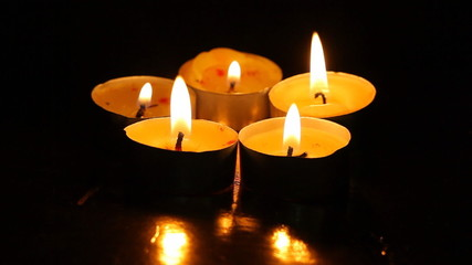 Five burning candles against a dark background with reflection