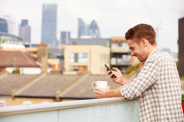 Man Using Mobile Phone On Rooftop Garden Drinking Coffee