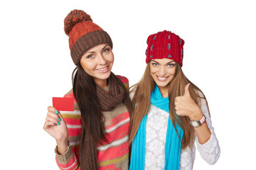 Two winter girls showing blank card