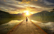 Leinwanddruck Bild - Traveler walking along the road to the mountains