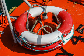 Close-up of a red and white weatherd life-belt (buoyancy aid) on