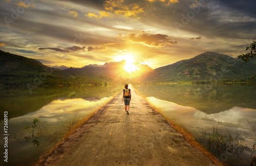 Leinwanddruck Bild Traveler walking along the road to the mountains