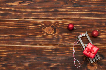 Christmas Decorations. Gift Box On Sleigh. Wooden Background