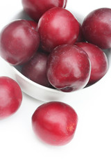 prugne rosse su sfondo bianco_ frutta