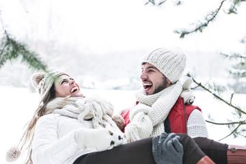Mann trägt lachende Frau im Winter
