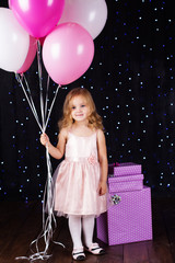 Little girl with pink balloons and gift boxes