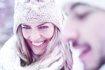 Frau und Mann lachen im Winter im Schnee