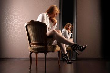 Frau sitzt im Sessel vor einem Spiegel