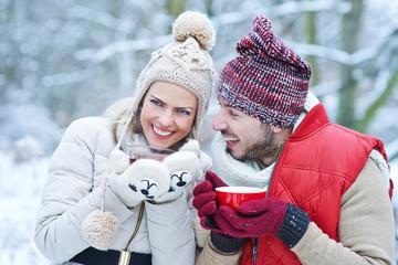 Paar mit Tee im Winter beim Lachen